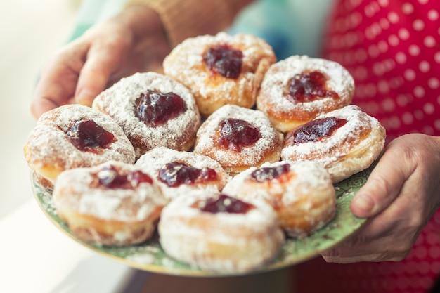 잼이 가득한 도넛으로 가득 찬 접시에 설탕을 입힌 노파가 손에 들고 있습니다.