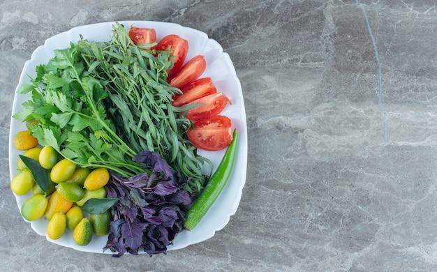 대리석 테이블에 혼합 야채로 가득 찬 접시.