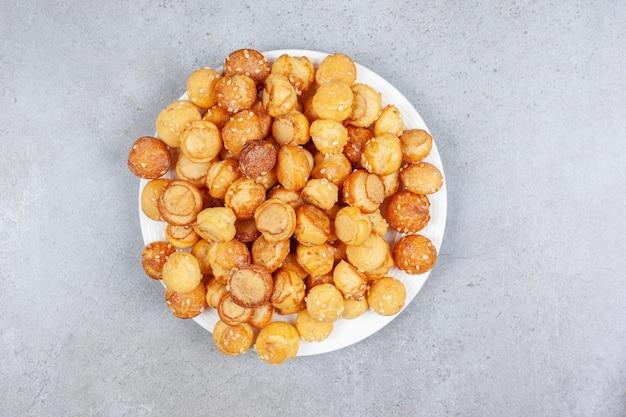 Un piatto pieno di piccoli biscotti su fondo in marmo. foto di alta qualità