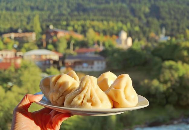 Plate of georgian traditional soup dumplings called khinkali in woman's hand