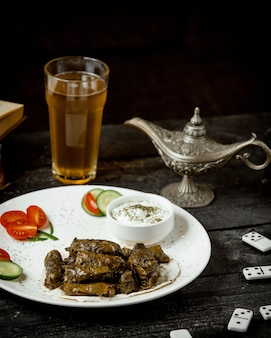 A plate of grape leaves dolma served with yogurt cucumber and tomato