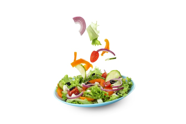 Plate of greek salad and ingredients isolated on white