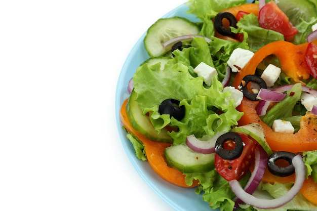 Plate of greek salad isolated on white surface