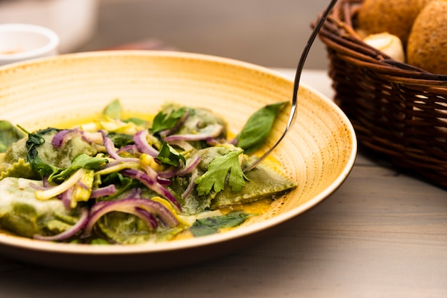 Plate of green ravioli pasta with onion and coriander leaves