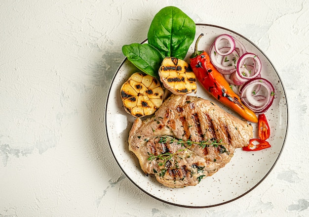 Plate of grilled pork steak with vegetables on concrete background