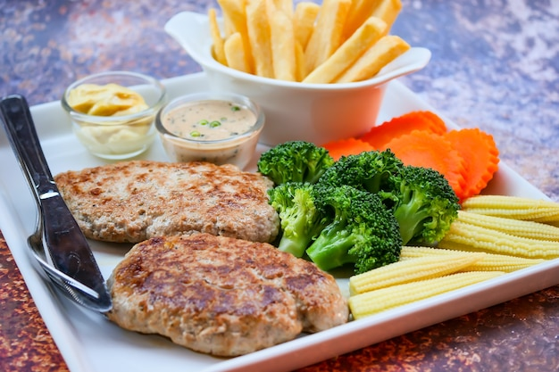 Plate of grilled pork with french fries and salad