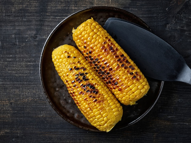 Plate of grilled sweet corn on black wooden kitchen table, top view