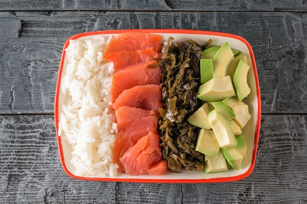 A plate of hawaiian rice, avocado, salmon and kelp on a rustic gray table. the view from the top.