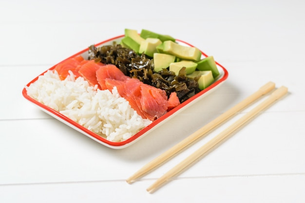 A plate of hawaiian rice, avocado, salmon, and kelp.
