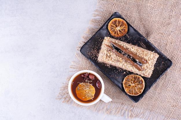 Piatto di torta fatta in casa con tè alla frutta su tela. foto di alta qualità