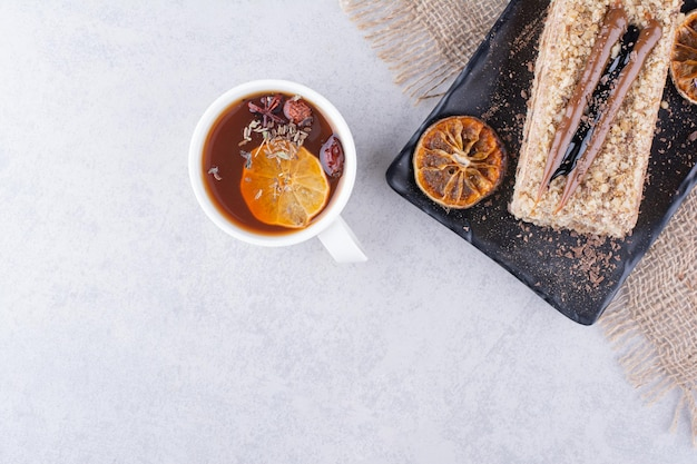 Plate of homemade cake with fruit tea on marble surface.