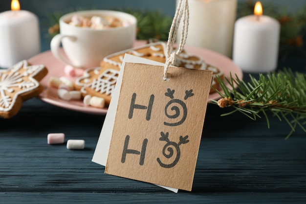 Plate of homemade christmas cookies, coffee, marshmallows, ho-ho on wooden table, on blue, space for text. closeup