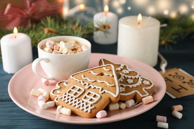 Plate of homemade christmas cookies, coffee, marshmallows on wooden table, on blue, space for text. closeup