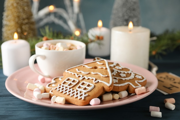 Plate of homemade christmas cookies, coffee, marshmallows on wooden table, on blue, space for text. closeup Premium Photo