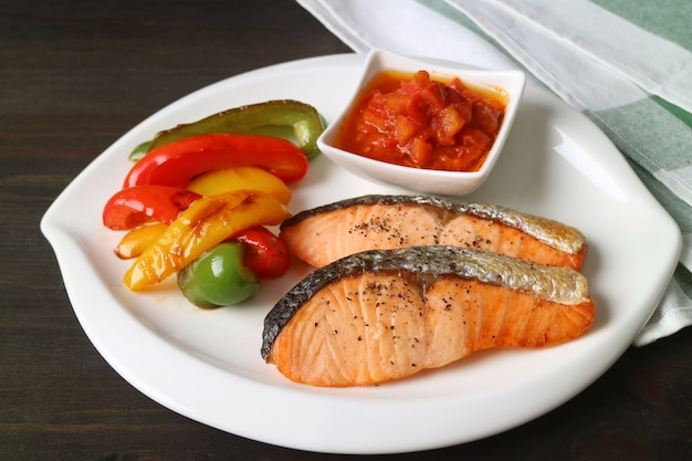 Plate of homemade pan seared salmon steaks with colorful grilled bell-peppers