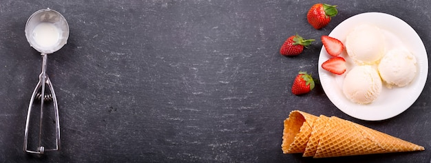 Plate of ice cream scoops with fresh strawberry and waffle cones on dark , top view with copy space