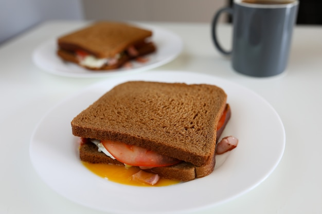 On plate is sandwich dark bread with sausage