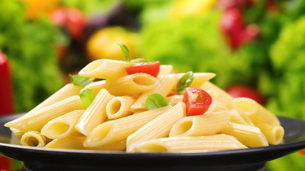 Plate of italian penne rigate pasta with tomatoes and basil leaves,