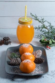 Plate of juicy tangerines decorated with powder and pinecones and jar of juice.