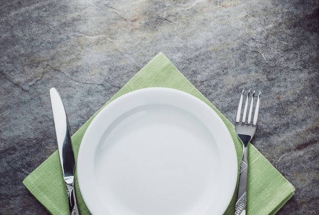 Тарелка, нож и вилка на салфетке