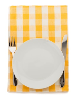 Plate, knife and fork at napkin on white background