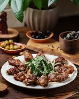 A plate of lamb entrecote ribs kebab with onions and greens