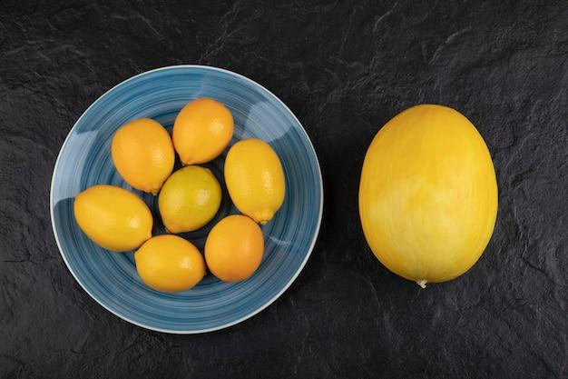 Piatto di limoni e melone maturo posto sul tavolo nero.