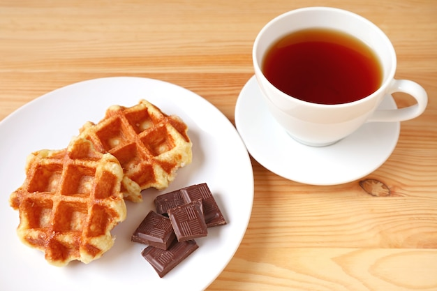 Plate of liege waffles with dark chocolate chunks and a cup of hot tea on wooden table