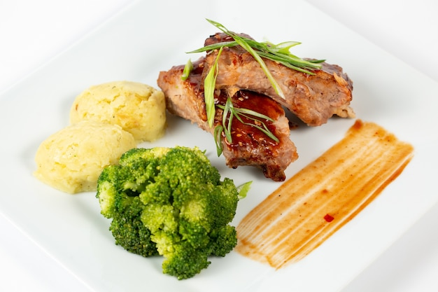 Plate of meat with barbecue sauce mashed potatoes and broccoli
