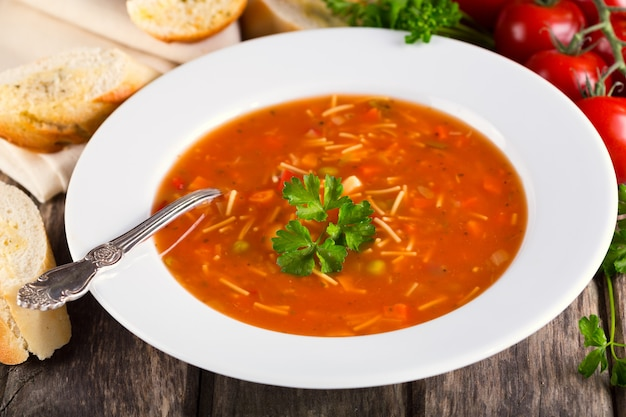 Plate of minestrone soup on wooden table