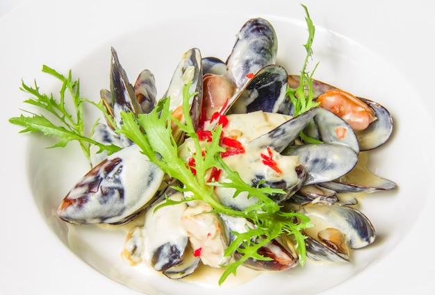 Plate of mussels in sauce with fresh herbs. restaurant shot.