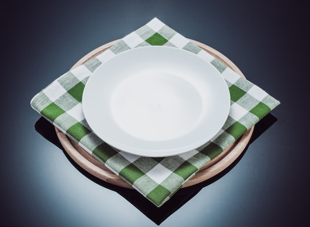 Plate, napkin cloth and pizza cutting board at glossy black background