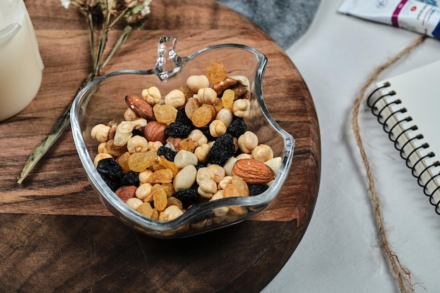 A plate of nuts with candle, flower, paper and tubes on wooden board.