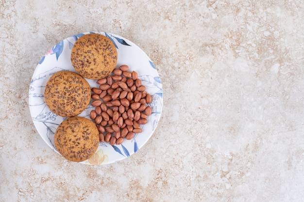 Plate of oatmeal cookies and peanut kernels on marble surface.