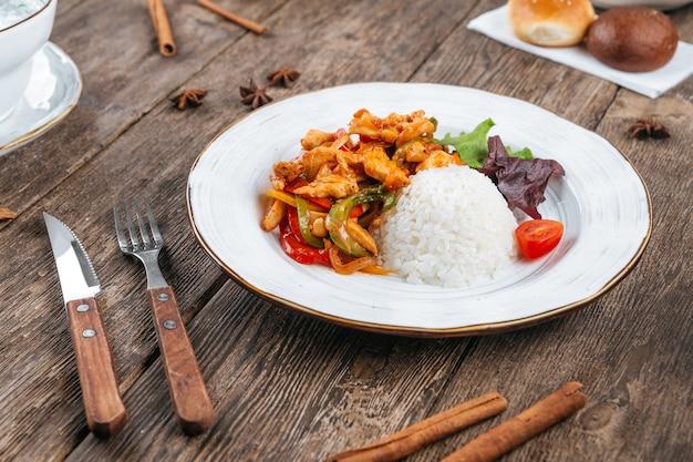 Тарелка азиатской жареной курицы с овощами и рисом