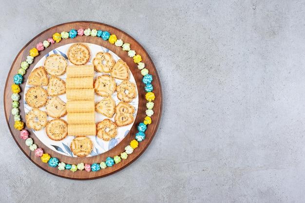 大理石の背景の木の板にポップコーンキャンディーで囲まれた各種クッキーのプレート。高品質の写真