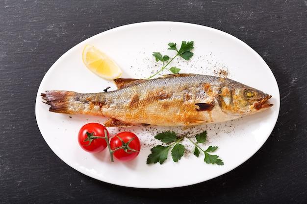 어두운 배경, 평면도에 야채와 함께 구운 생선 접시