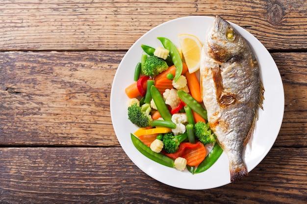 나무 테이블, 평면도에 야채와 함께 구운 생선 접시