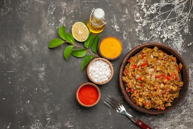 豆とスパイスのプレートカラフルなスパイスのボウルレモンオイルのボトル暗いテーブルの上の緑の豆のプレート