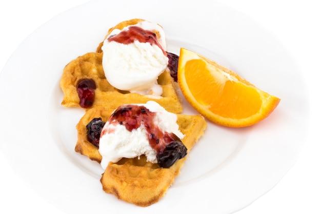 アイスクリーム、ジャム、白地にオレンジのスライスとベルギーワッフルのプレート。