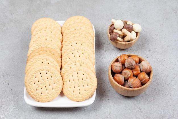 Тарелка печенья рядом с мисками лесного ореха и шоколадных грибов на мраморном фоне. фото высокого качества
