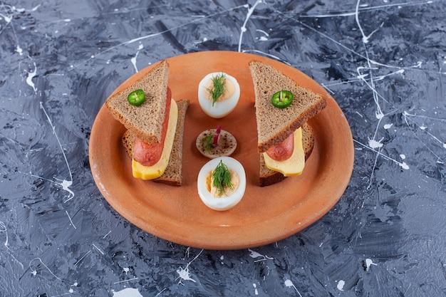 大理石の表面にチーズとトマトが入った黒いパンのスライスのプレート。
