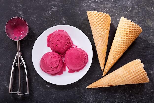 Тарелка совков черничного мороженого и вафельных рожков на темном фоне