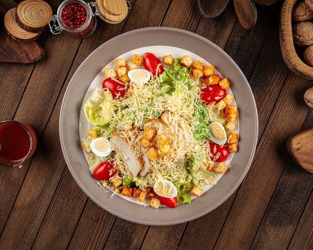 Тарелка салата цезарь с курицей и листьями салата