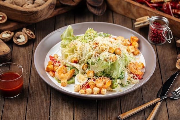 Тарелка салата цезарь с креветками и салатом