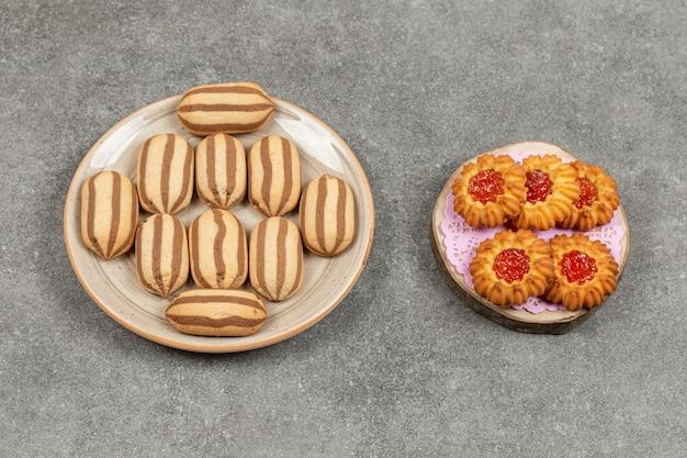 대리석 표면에 초콜릿 스트라이프 비스킷과 젤리 비스킷 접시
