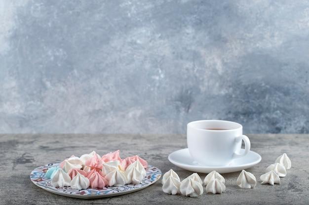 다채로운 달콤한 머랭 사탕과 돌 배경에 차 한잔 접시.