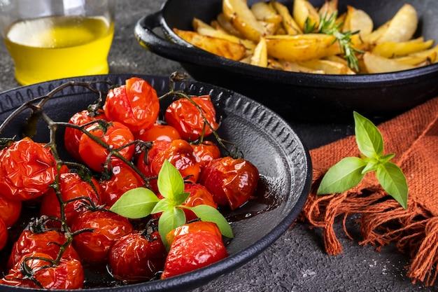 暗い背景に鉄のキャセロールでローズマリーとコンフィトマトとローストポテトのプレート。