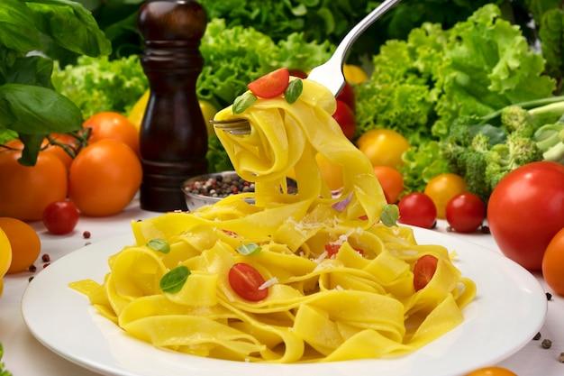 요리 이탈리아 페투치니 파스타 접시, 토마토와 바질 잎 포크에 tagliatelle