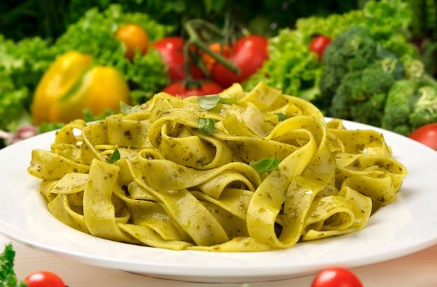 調理されたイタリアのフェットチーネパスタとペストソースのプレート